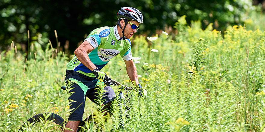 Noah Hoffman riding his bike on a grassy field.