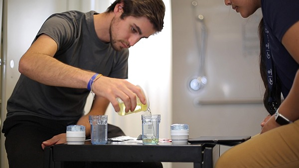 Young white male pouring urine into a sample collection cup in view of doping control officer.