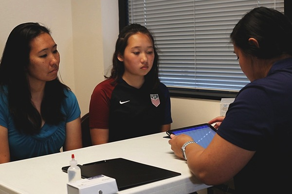 Young asian female athlete with mother talking to a doping control officer at a table.