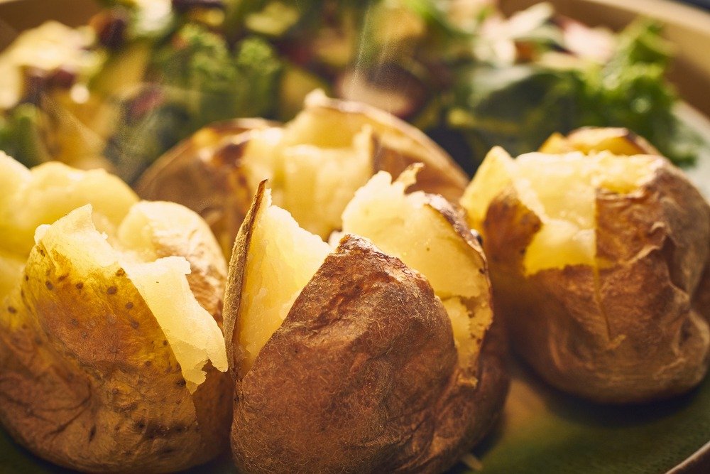 Cut open baked potatoes.