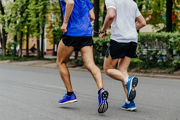 Two male athletes running connected by a chain as one athlete is blind.