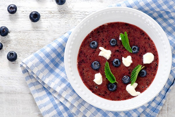 Blueberry soup in a white bowl.
