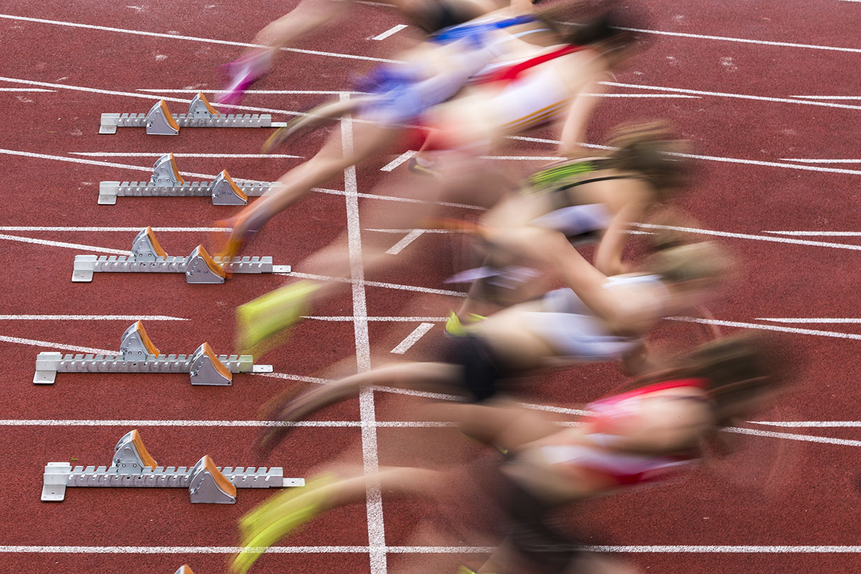 blurry track and field sprinters pushing off starting blocks