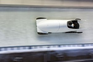 white bobsled with two athletes going down a luge track