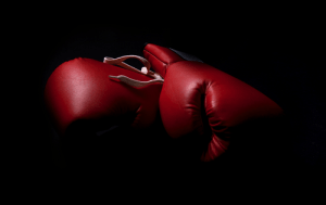 two boxing gloves in the shadows