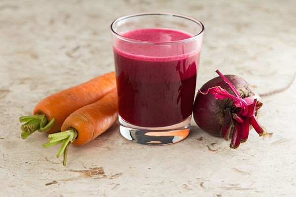 Glass of dark red liquid next to carrots and a beet.
