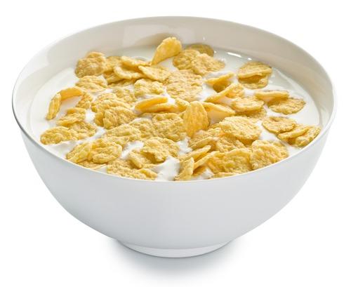 corn flakes in milk in white bowl