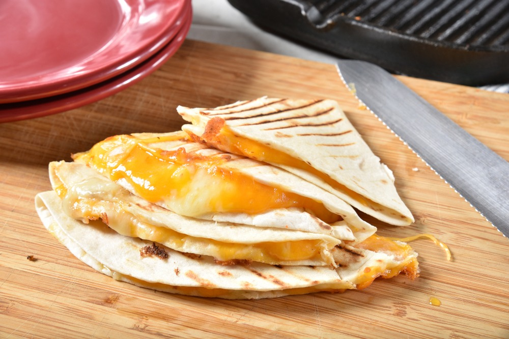 A cheese quesadilla next to a knife.