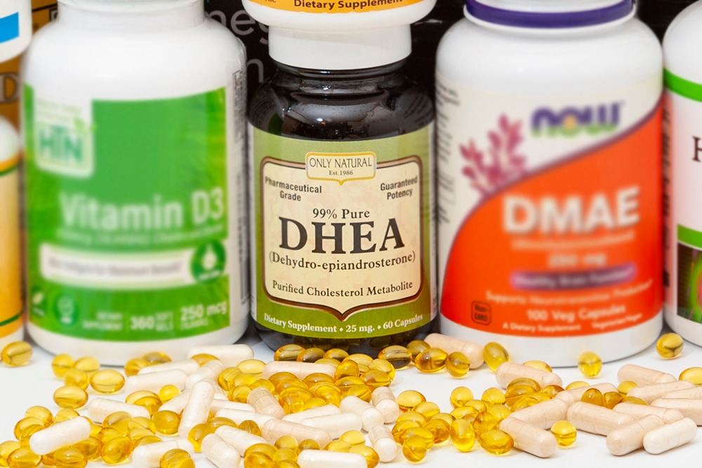 DHEA Supplement bottle with various pills next to the bottle.