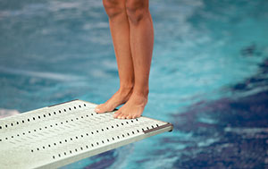 view of female athletes below knees on a diving board