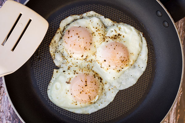 three eggs over easy in a pan