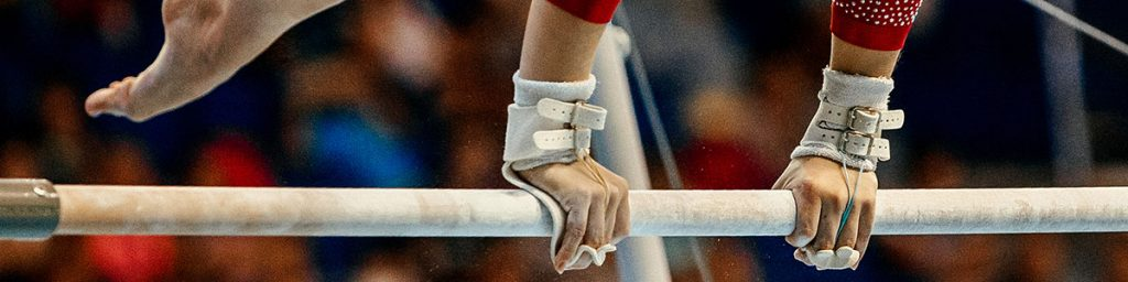 close-up of female gymnastics hands on uneven bars