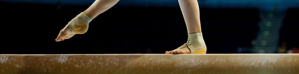 Female gymnast walking on balance beam.