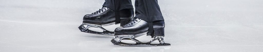 close up of male figure skater's skates on ice