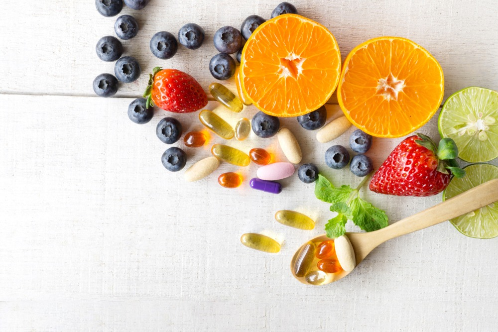 Fresh fruits on a table next to supplement pills.