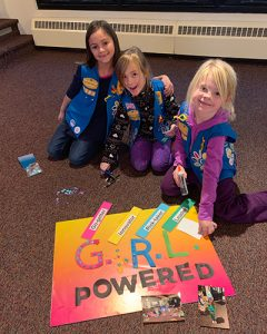 young girl scouts making a poster