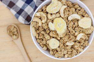 white bowl full of granola and sliced banana