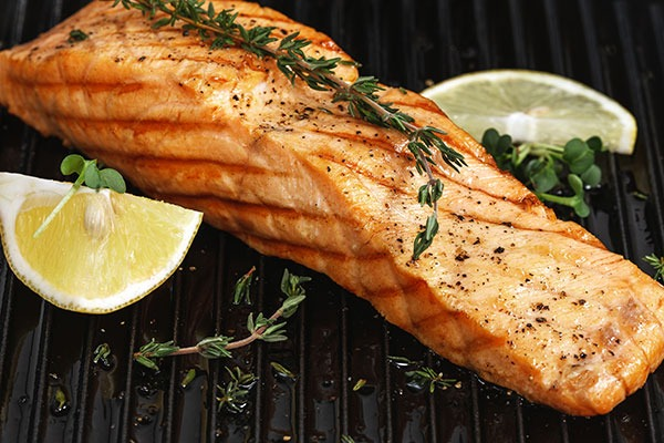 Grilled salmon next to sliced lemon.