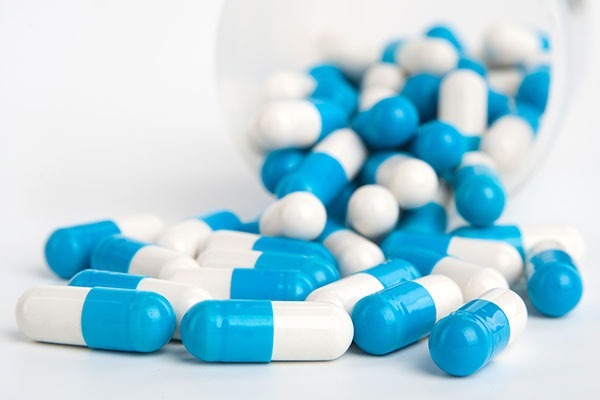 blue and white capsules on white background