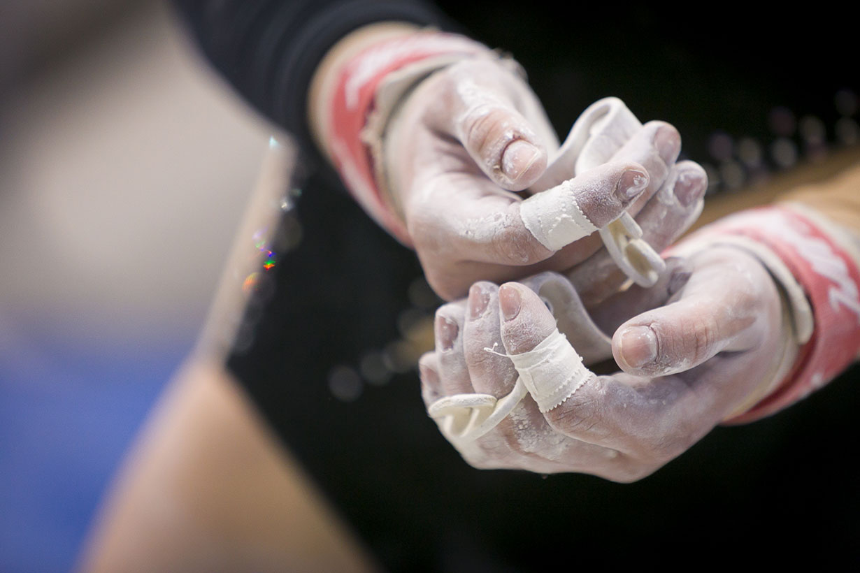 hands of gymnast covered in chalk and athletic tape