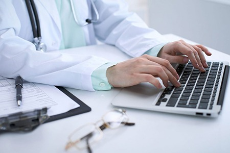 doctor at desktop computer typing on keyboard