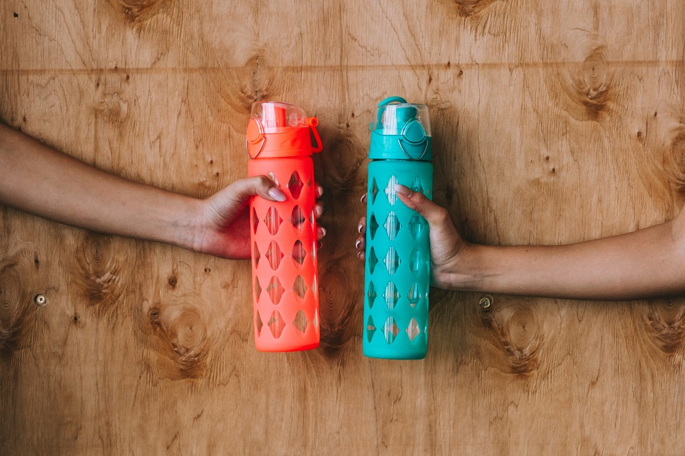 Two hands holding different colored reusable sport water bottles.