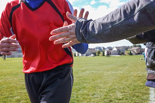 Young athlete high fiving a parent on the sideline (close-up of hands.)