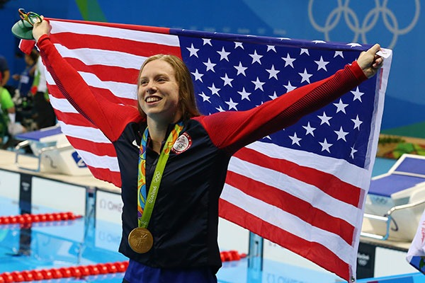 Lilly King holding the United States Flag while at the Olympics with a medal around her neck.