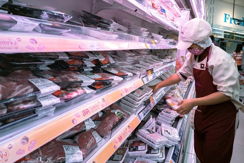 Worker putting meat on shelves in a grocery store in Bangkok.