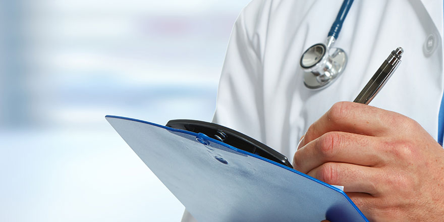 medical doctor writing on clip board