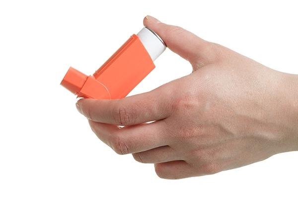 Hand holding an orange inhaler on a white background.