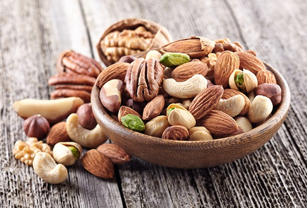 Various raw nuts in a wood bowl.