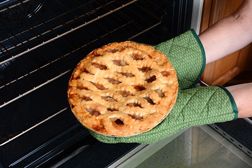 Close up of a pie coming out of an oven being held by a person wearing two green oven mitts.