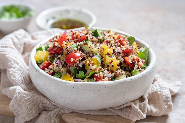 Quinoa salad with vegetables in a white bowl.