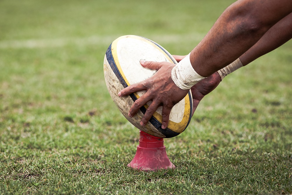 Man setting up a rugby oval to kick.