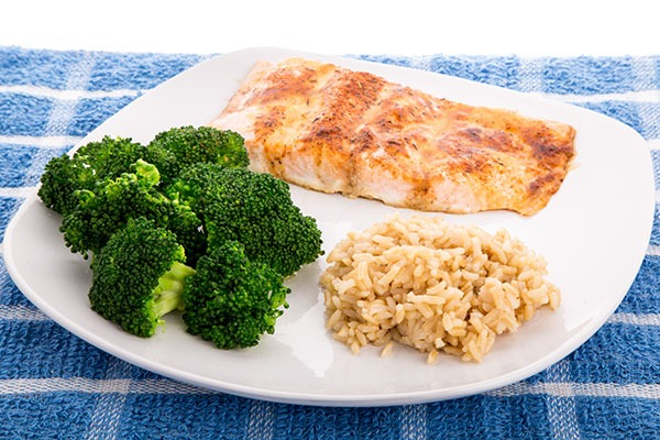 Plate of grilled salmon with brown rice and steamed broccoli