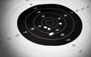 image of paper target full of bullet holes