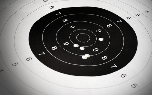 image of paper target full of bullet holes