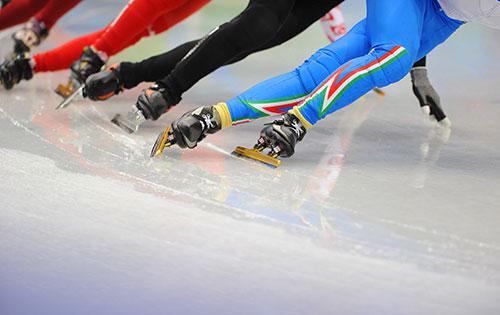 speedskaters going around a corner on the ice track