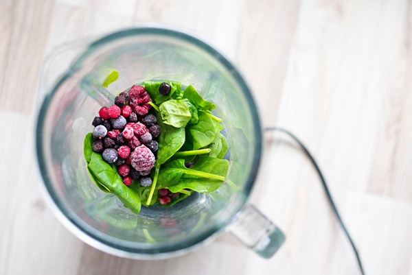 Shot fro above of spinach and frozen berries in a blender.