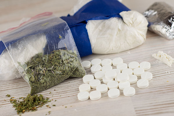 A table top with a bag of heroin, a clear bag of cocaine, a small bag of marijuana, and small, circular white pills.