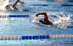two swimming racing in lanes in a pool