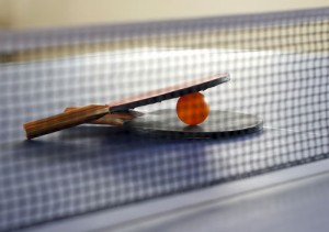 table tennis paddles with ball on table