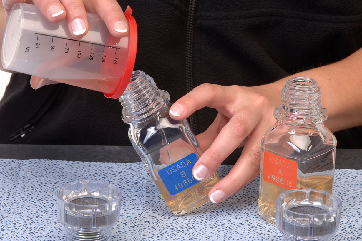 Female pouring sample into A and B bottles