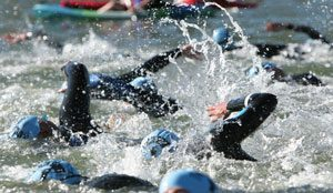 group of people swimming in a triathlon