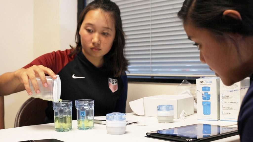 Youth athlete pouring urine into a collection vessel.