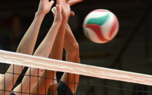 arms going up over a volleyball net to block the ball