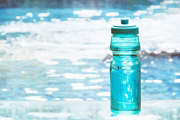 blue water bottle next to pool