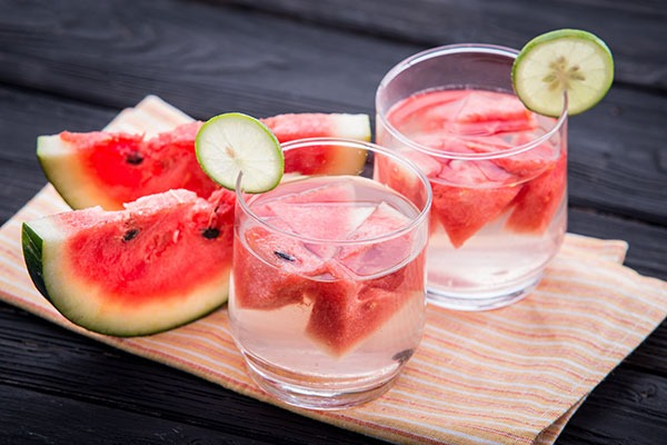 sliced watermelon on a wooden board next to two glasses of water with watermelon floating within