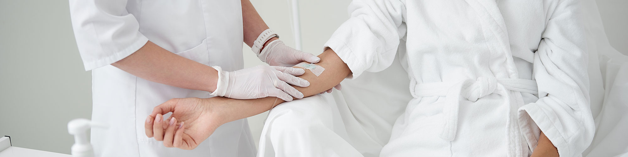 woman in robe receiving IV infusion at wellness clinic
